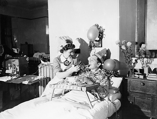 A nurse feeds a patient with a spoonful of Christmas pudding at a naval hospital at Kingseat in Scotland, December 1941. A6486