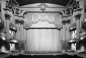 Joseph A. Bailly - Academy of Music, Philadelphia, Pennsylvania (1855-57). The cameo bust over the proscenium is of Mozart, with the goddesses of Music and Poetry above it; giant Atlases appear to hold up the ceiling.