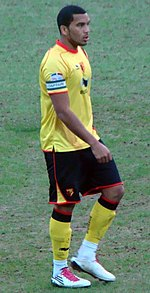 "A young man with short dark hair and a short, well maintained beard. He is wearing a yellow top and black shorts, both with red trim, yellow and black socks, and white footwear. He is standing on a grass field. On his forearm, he is wearing an armband; the word ""Captain"" is visible."