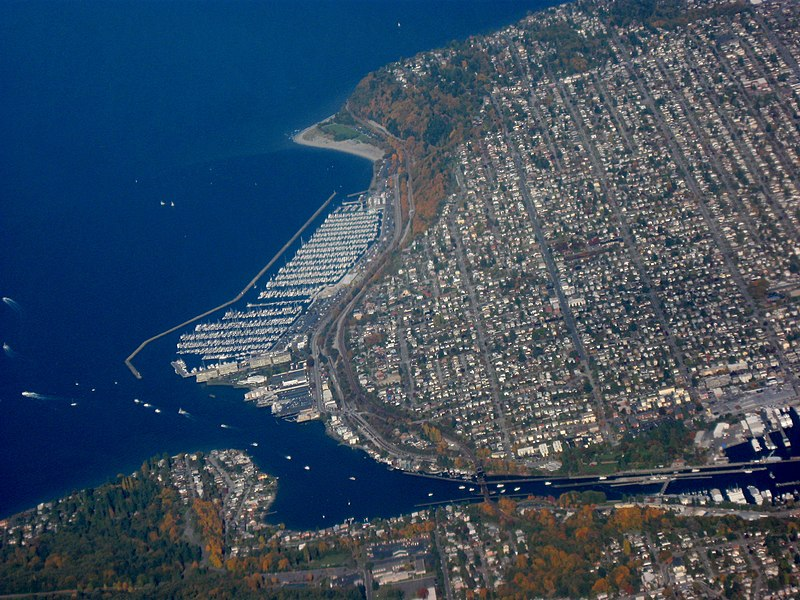 Aerial view of Seattle's Ballard neighborhood facing north. Lake Washington Ship Canal is seen to the south. Docks and marinas line Puget Sound's Shilsole Bay to the west. To the north is Golden Gardens Park. Photo credit Dcoetzee.