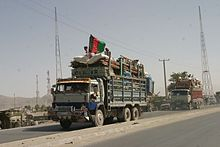 Two trucks full of household belongings, one with a black, red and green Afghan flag