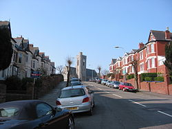 A typical street in Romilly, All Saints Church pictured at the top of the hill