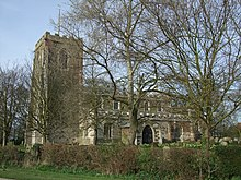 A stone church seen from the south, with a battlemented tower on the left, and a nave with clerestorey and porch to the right
