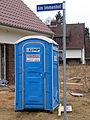 Am Immenhof, Celle, transportables Kunststoff-Toilettenhäuschen Olymp Toi Toi & Dixi Sanitärsysteme vor einem Neubau.jpg