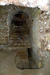 Vue d'un couloir voûté muni d'un escalier. Légende détaillée ci-dessous.