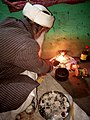 An old man of a village in Himachal Pradesh lighting the lamp( Diya) at shivratri occasion.jpg