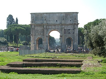 Landscape view of the Arch of Constantine across the Campus Martius with the via Sacra behind with trees and the Caelian Hill rising on the left and the Palatine Hill on the right.