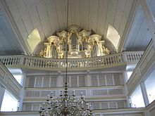 Interior of a church, facing the rear with the organ on the third tier. The organ prospect is decorated with small Baroque golden ornaments.
