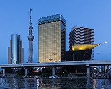 Asahi Breweries headquarters building with the Asahi Flame and Skytree at blue hour with full moon, Sumida-ku, Tokyo, Japan.jpg