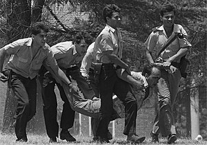 1989 attack on La Tablada barracks - Policemen dragging a wounded militant during the attack.