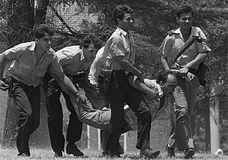 1989 attack on La Tablada barracks - Policemen dragging a wounded militant  during the attack