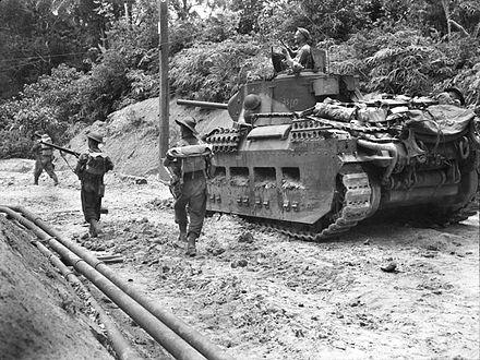 Australian infantrymen passing a tank in the interior of Tarakan Australian Matilda II tank supporting infantry during the attack on Skyes on Tarakan in May 1945 (AWM 089471).jpg