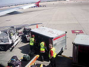 Baggage handlers loading a Northwest Airlines ...