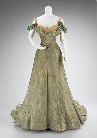 "Artistic Dress movement - Ball gown designed by Jacques Doucet, 1898-1900, with characteristics of the aesthetic dress movement : simple in design, ""yet extravagant by the choice of materials used. The sheer overlayer is enhanced by the solid lamé underlayers and a sense of luxury is added by the hidden lace flounce at the hem."""