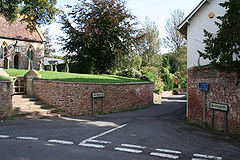 Road junction with house on the right of the road. On the left is a churchyard behind a wall accessed via steps.