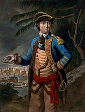 Arnold is shown wearing a military uniform: blue coat over buff waistcoat and trousers, red waistband, tricorner hat.  In the background a town is visible, as are trees that look something like palm trees.