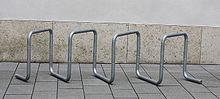 A free-standing bike rack, consisting of galvanized steel tubing bent into multiple square loops set at 45 degrees, on concrete slabs in front of a concrete wall