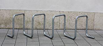 Отдельно стоящая стойка для велосипедов, состоящая из оцинкованной стальной трубы, изогнутой в несколько квадратных петель, установленных под углом 45 градусов, на бетонных плитах перед бетонной стеной.