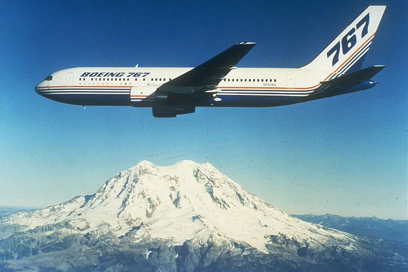 Boeing twin engine jetliner in flight near a snow-capped mountain.