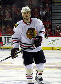 Hockey player in white uniform. He stands in a relaxed stance, one foot slightly off the ground.