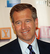A head shot of Brian Williams, a caucasian male in his late-40s with dark hair. He smiles, and wears a black suit with a white shirt and purple and black-striped tie.