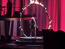 Image of a blond woman. She is standing in the middle of a fiery ring, wearing a black, white and gold outfit, with a pink led screen in front of her. A guitarist can be seen on her left.