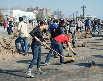 Volunteering - Volunteers sweep the boardwalk in Brooklyn after the 2012 Hurricane Sandy.
