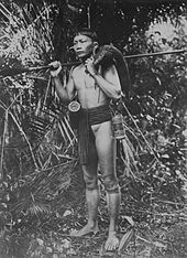 Retrato de um caçador Dayak em Bornéu com um javali nos ombros