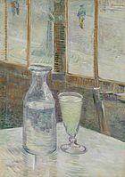 A glass and bottle on a cafe table