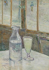 A glass and bottle on a café table