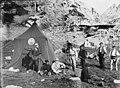 Campament de cacera amb una tenda de campanya i dos homes portant un isard mort.jpeg