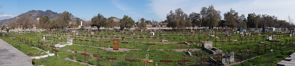 Rows of graves with metal crosses for headstones, a mountain in the distance