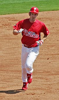 "A man in white pants, a red baseball jersey with ""Phillies"" on the chest, and a red batting helmet with ""P"" on it runs on a dirt surface."
