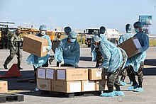 Workers unloading boxes of medical supplies at Villamor Air Base