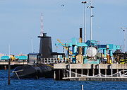 A submarine next to a dock, which is occupied by several cranes and other mechanical equipment
