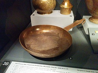 Frying pan - Copper frying pan dated 5th to 4th century B.C., Archaeological Museum of Thessaloniki. The handle is ornamented with floral engravings and ends up in the shape of a goose head.