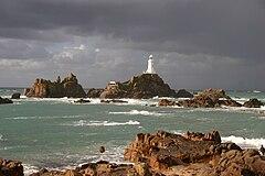 Zdjęcie przedstawia znajdującą się na niewielkiej skalnej wysepce latarnię morską. Latarnia morska pomalowana jest na biało. Koło wysepki z latarnią znajduje się wiele innych małych, skalistych wysp. Wszystkie wyspy otacza lekko wzburzone morze