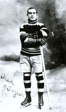 A young man poses for a photo, wearing a sweater, skates, and holding an ice hockey stick on his left side
