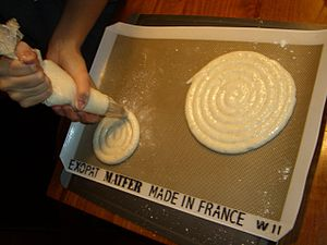 Pastry bag - Piping dacquoise meringue disks onto a baking sheet.
