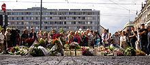 Foto einer Menschenmenge hinter niedergelegten Blumenkränzen und Kerzen