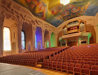 Goetheanum - Performance hall showing carved columns, stained-glass windows, and painted ceiling