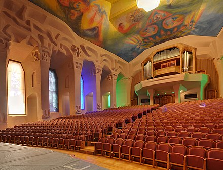 Performance hall showing carved columns, stained-glass windows, and painted ceiling Dornach - Goetheanum - Grosser Saal3.jpg