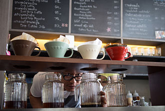 Brewed coffee - Coffee drips through beans and filters into several jars in this specialty coffee shop.