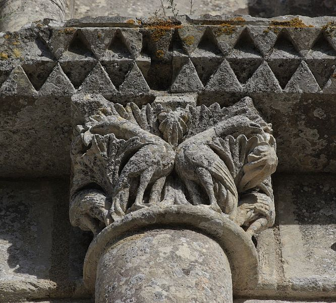 Carved capital and damaged frieze, romanesque church of Échebrune (XIIth and XVth centuries), first stage of the facade. Échebrune, Charente-Maritime, France.
