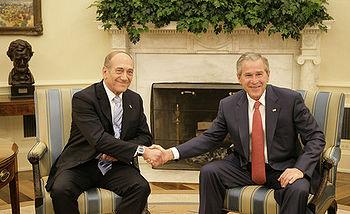President George W. Bush exchanges handshakes ...