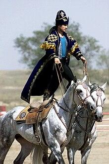 Kazakh en costume traditionnel, debout sur deux chevaux en mouvement.