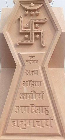 Relieve de piedra bronceada de la esvástica jainista y sus cinco votos