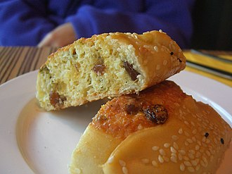 Flaouna - A flaouna halved, showing both the sesame seed topping and the raisins inside