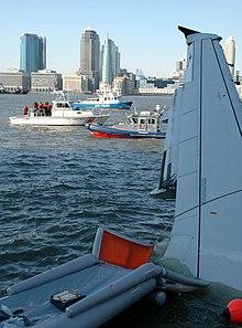 Photo de l'avion amarrée sur la rive. La photo, prise depuis l'intérieur de l'avion, montre l'aile et un toboggan d'évacuation ainsi que la ville de New York à l'arrière-plan.