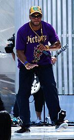 Flo Rida rapping in a concert, wearing a purple shirt, sweatpants, and a cap.